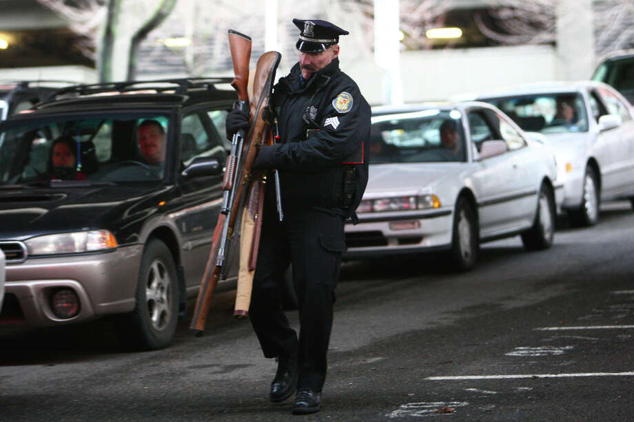 Seattle Police Sgt. Paul Gracy carries weapons turned in during the City of Seattle's gun buy back program on Saturday, January 26, 2013. The program handed out $80,000 worth of gift cards in exchange for weapons brought in by the public. Photo: JOSHUA TRUJILLO, SEATTLEPI.COM / SEATTLEPI.COM