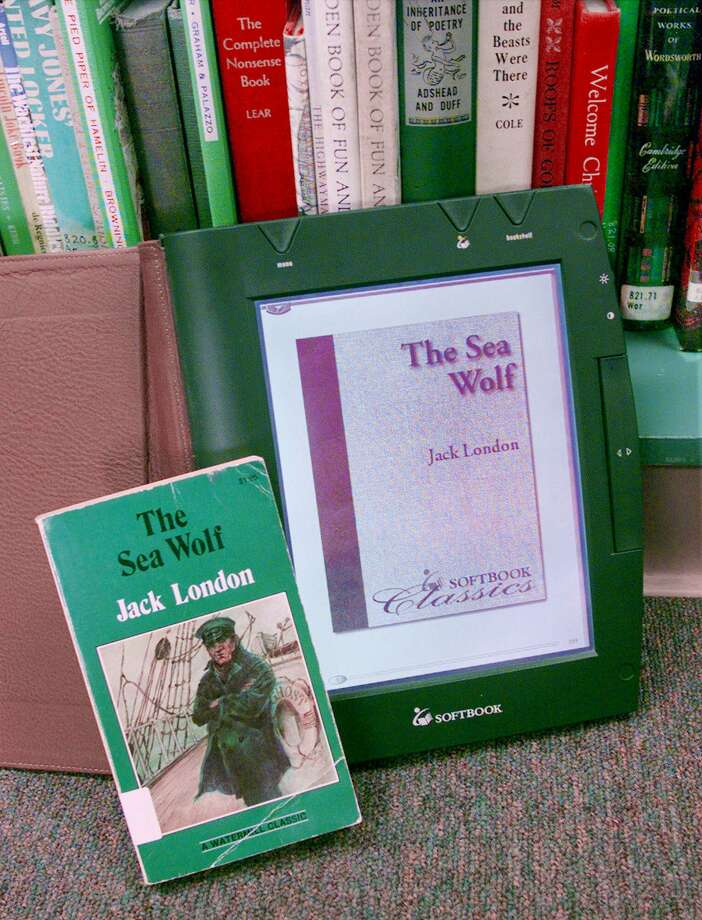 ADVANCE FOR MONDAY, AUG. 30--Displayed is the SoftBook eBook with a display of the cover of Jack London's book 'The Sea Wolf' next to the soft-bound book in a San Jose, Calif., library, Thursday, July 22, 1999.  Electronic books are portable devices about the same size as a regular book that holds more than 10 books, magazines or newspapers at a time. (AP Photo/Paul Sakuma) Photo: PAUL SAKUMA, STF / AP