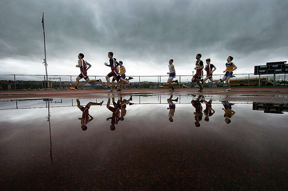 The 800-meter splash: Runners from Valley View and Scranton high schools sprint by a puddle in the 800m race during a track meet in Scranton, Pa. Photo: Butch Comegys, Associated Press
