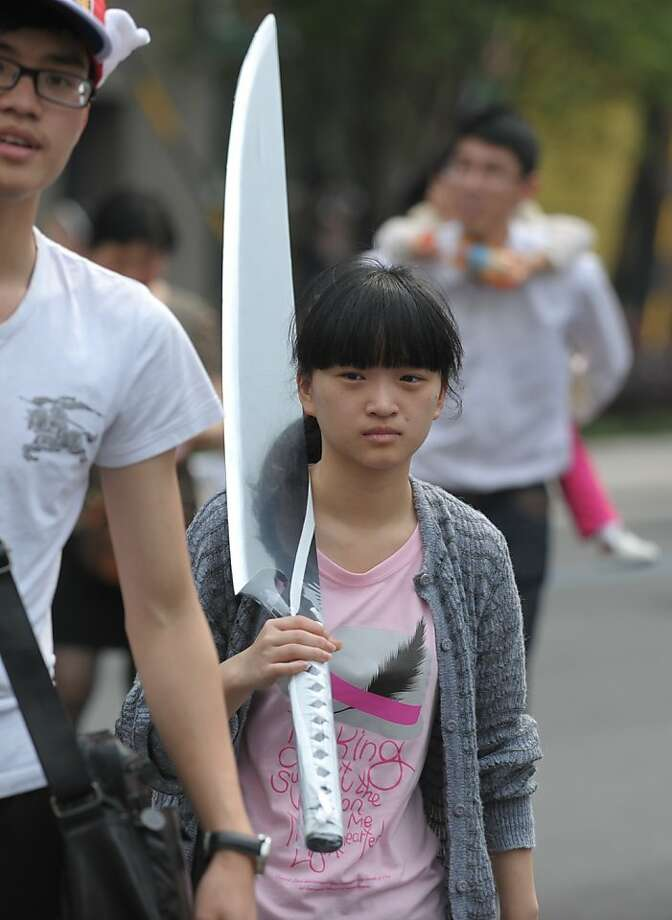 Don't look now, but you're being followed by a girl carrying the world's largest chef's knife. (China International Cartoon and Animation Festival in Hangzhou.) Photo: Peter Parks, AFP/Getty Images
