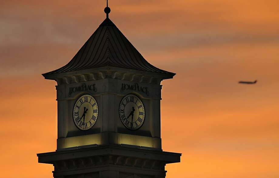 Time flies: A passenger jet rises behind the Home Place clock tower at sunset in Prattville, Ala. Photo: Lloyd Gallman, Associated Press