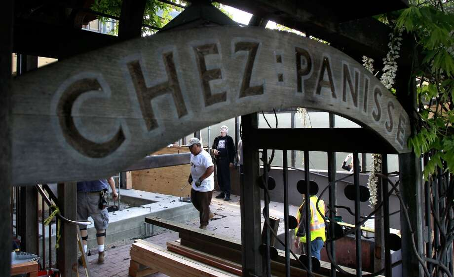 Workers bolt the 1800-pound frame to the foundation as it is put into place on the front porch of Chez Panisse in Berkeley this morning.