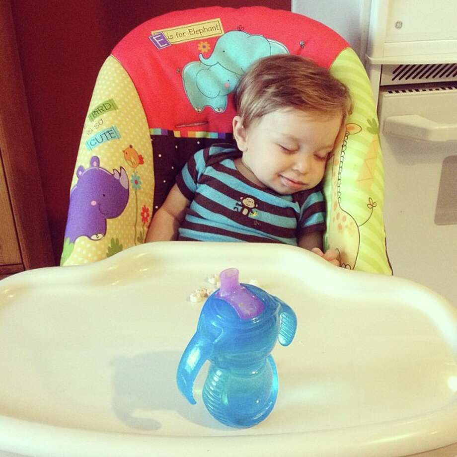 Greyson in his high chair by Lauren Ledford. It seems he's dreaming about his tasty meal.