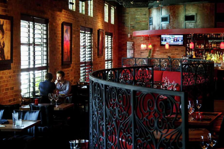 Awash in crimson and wrought iron, La Casa del Caballo's dining room is comfortable and warm. Photo: Michael Paulsen, Staff / © 2013 Houston Chronicle