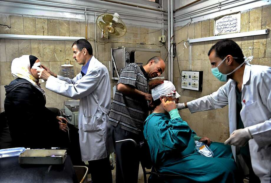 In this photo released by the Syrian official news agency SANA, Syrian doctors treat citizens who were injured in an  explosion, in the central district of Marjeh, Damascus, Syria, Tuesday April 30, 2013. A powerful explosion rocked Damascus on Tuesday, causing scores of casualties, a day after the country's prime minister narrowly escaped an assassination attempt in the heart of the heavily protected capital. (AP Photo/SANA) Photo: Uncredited, Associated Press