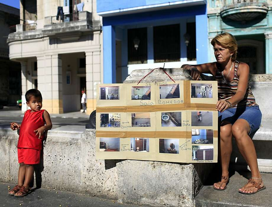 Estrella Diaz sits next to a homemade sign advertising her Havana home for sale last month. A baffling real estate market has emerged in Cuba since the legalization of private home sales. Photo: Franklin Reyes, Associated Press
