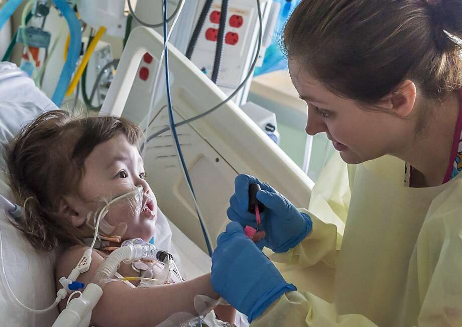 In this April 26, 2013 photo provided by OSF Saint Francis Medical Center in Peoria, Ill., Hannah Warren, 2,  looks up as nurse Bethany McGfraw paints her fingernails in a post-op room at Children's Hospital of Illinois in Peoria. Hannah received a new windpipe in a landmark windpipe operation April 9, 2013. She was born in South Korea without a windpipe but received a new one made from her own stem cells. She is the youngest patient ever to get the experimental treatment. Doctors announced Tuesday, April 30, 2013, she is recovering and likely will lead a normal life. (AP Photo/Courtesy of OSF Saint Francis Medical Center, Jim Carlson) Photo: Jim Carlson, Associated Press