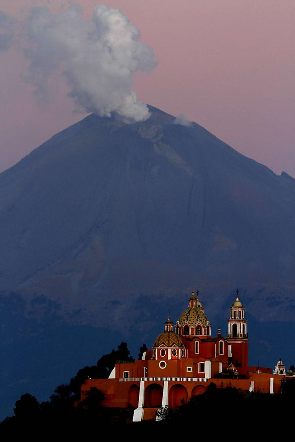A plume of ash and steam rise from the Popocatepetl volcano overshadowing the Catholic church Nuestra Señora de los Remedios or Our Lady of Remedies in Cholula, in the Mexican state of Puebla, Sunday, April 22, 2012. Popo, as the volcano is commonly known, has put out small eruptions of ash almost daily since a round of eruptive activity began in 1994. A week ago, the eruptions started growing larger. Authorities prepared evacuation routes, ambulances and shelters in the event of a bigger explosion. (AP Photo/Marco Ugarte)
