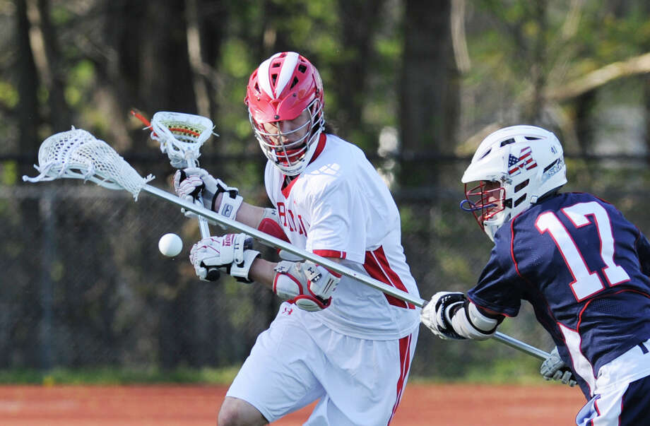 At right, Finn Maloney (#17) of Brien McMahon stick-checks the ball from Kyle Foote of Greenwich durng the boys high school lacrosse match between Greenwich High School and Brien McMahon High School at Greenwich, Tuesday, April 30, 2013. Photo: Bob Luckey / Greenwich Time