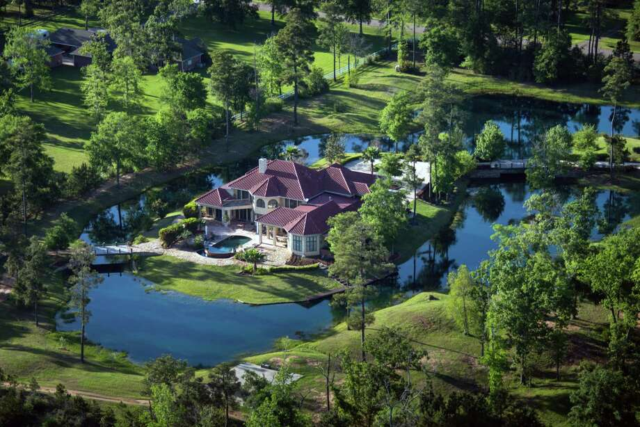 The home J. Jesus Gallegos Alvarez,  a self-made multi-millionaire, who lived quietly for the last seven years of his life in self-imposed exile in a Woodlands area mansion complete with a moat, is seen in an aerial view on Thursday, April 11, 2013, in Houston. Gallegos Alvarez  was the visionary developer behind a glittering empire of Mayan-inspired palatial condo and hotel complexes in nearly every major Mexican coastal resort. In 2006, after what the Mexican press has described as organized crime-related threats, Alvarez abruptly ended his relationship with a major Mexican hotel chain and left his native Mexico and re-established himself in Houston's northern suburbs, forming a string of corporate U.S. entities that helped conceal his whereabouts and activities. In March, Gallegos Alvarez returned to Mexico in triumph as the newly-named Secretary of Tourism at the invitation of Jalisco's Governor-elect. Eight days later, he was assassinated in broad daylight on a street outside Guadalajara, and investigators are now probing whether his many international commercial activities are behind his still unsolved murder. Photo: Smiley N. Pool, Houston Chronicle / © 2013  Houston Chronicle