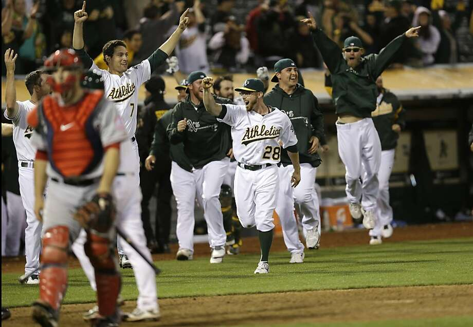 The Oakland Athletics celebrate a game- winning two-run home run by Brandon Moss during the nineteenth inning of a baseball game against the Los Angeles Angels on Tuesday, April 30, 2013 in Oakland. Calif. Oakland won 10-8 in 19 innings. (AP Photo/Marcio Jose Sanchez) Photo: Marcio Jose Sanchez, Associated Press