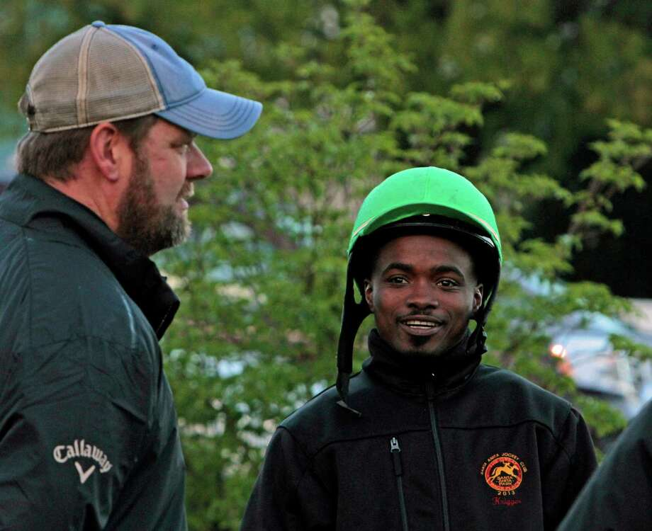 Jockey Kevin Krigger, right, talks with trainer Doug O'Neill, left, as they watch horses work out at Churchill Downs, Sunday, April 28, 2013, in Louisville, Ky. Krigger is to ride Kentucky Derby hopeful Goldencents for O'Neill in the race. (AP Photo/Garry Jones) Photo: Garry Jones / FR50389 AP