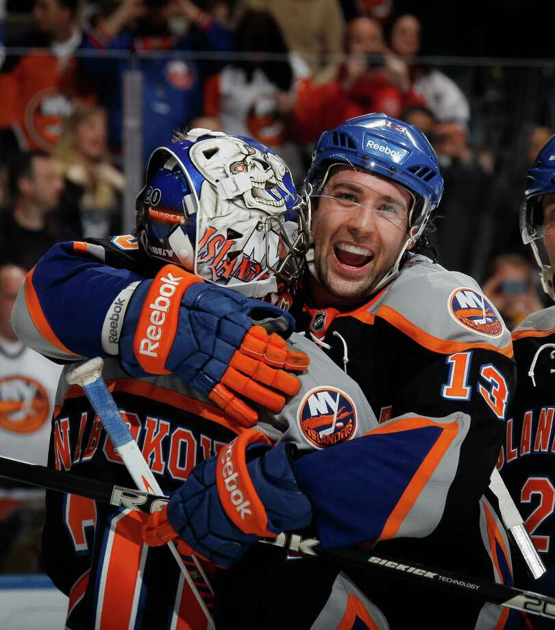 UNIONDALE, NY - APRIL 06: Colin McDonald #13 of the New York Islanders hugs goaltender Evgeni Nabokov #20 following their 4-2 victory over the Tampa Bay Lightning at the Nassau Veterans Memorial Coliseum on April 6, 2013 in Uniondale, New York.  (Photo by Bruce Bennett/Getty Images) Photo: Bruce Bennett, Getty Images / 2013 Getty Images