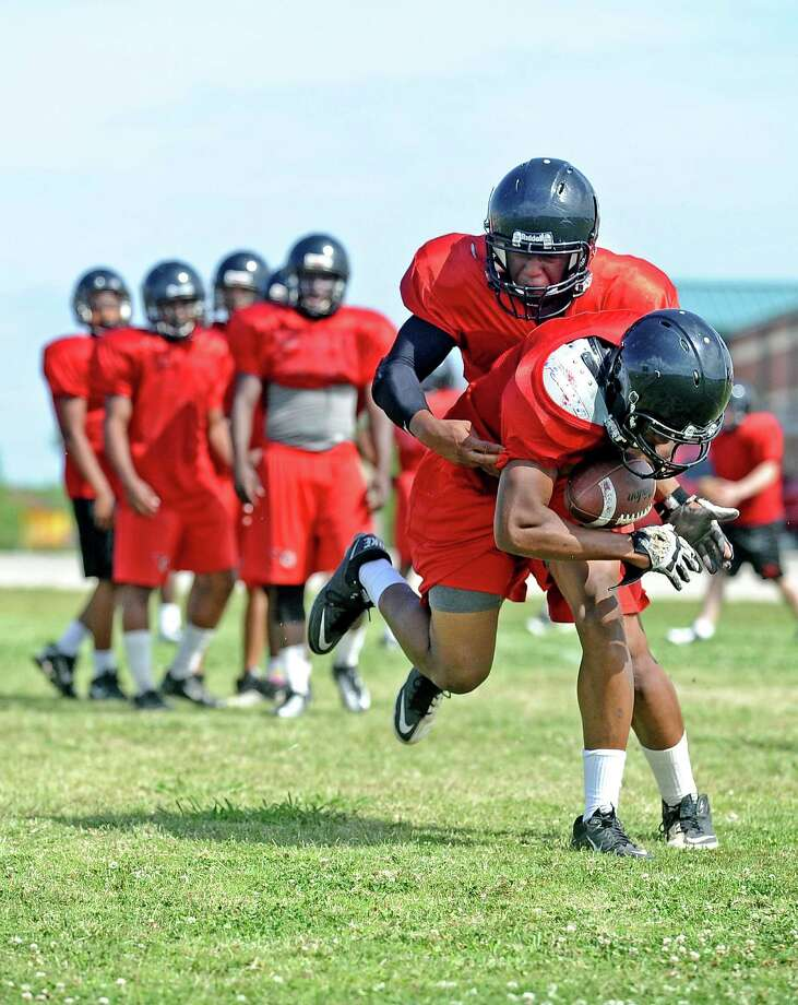 Junior Port Arthur Memorial High School football player Melbrodrick Matthews, behind, fights to strip the ball from his brother Meldric Matthews, front, while running defensive drills during the first day of spring practice on Tuesday, April 30, 2013, in Port Arthur. Photo taken: Randy Edwards/The Enterprise Photo: Randy Edwards