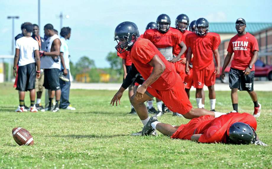 Junior Port Arthur Memorial High School football player Melbrodrick Matthews, center, leaves his brother Meldric Matthews on the ground while running defensive drills during the first day of spring practice on Tuesday, April 30, 2013, in Port Arthur. Photo taken: Randy Edwards/The Enterprise Photo: Randy Edwards