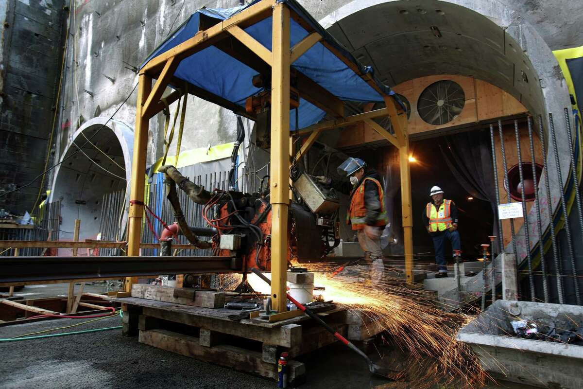 Rail worker Hector Mendez uses a machine to