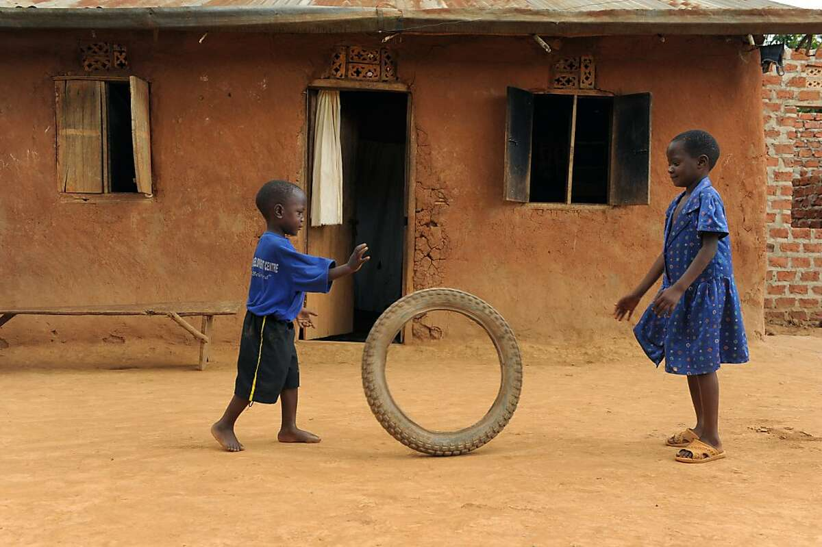 Nicolas, age 4, left, and his sister (name unavailable) play in front of their home in Uganada. Nicholas was 6 months old when his mother abandoned the family. He has been in Compassion's program for 2 years.