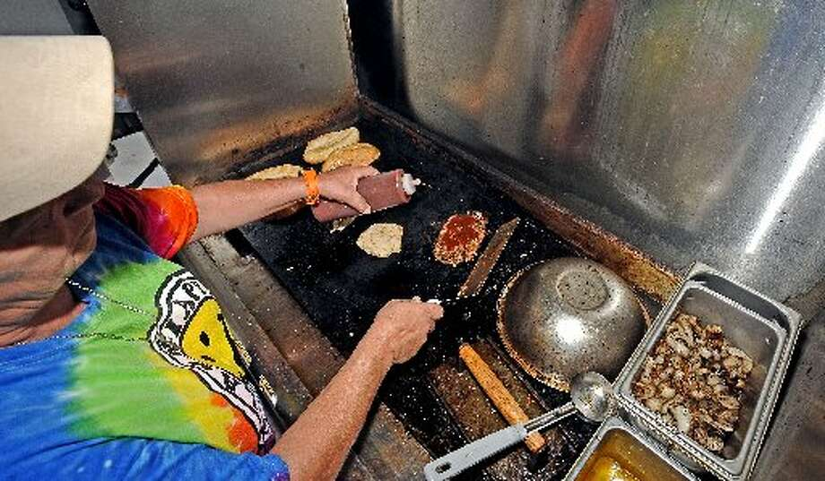 Robin Cappel prepares a pulled pork sandwich inside the Lagniappe at Yummo's food truck. Randy Edwards/cat5