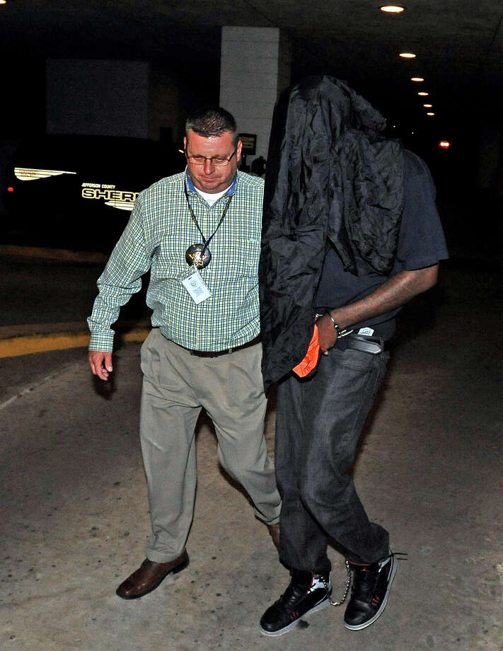 Royce E. Davis, 31, of Baytown is escorted out of the Jefferson County Court House with his jacket over his face on Tuesday, April 30, 2013.  Davis is being charged with the murder of 51-year-old Kimberly Grant of Crosby.  Grant's body was found on April 19, 2013, on a hunting lease off Tram Road. Photo taken: Randy Edwards/The Enterprise