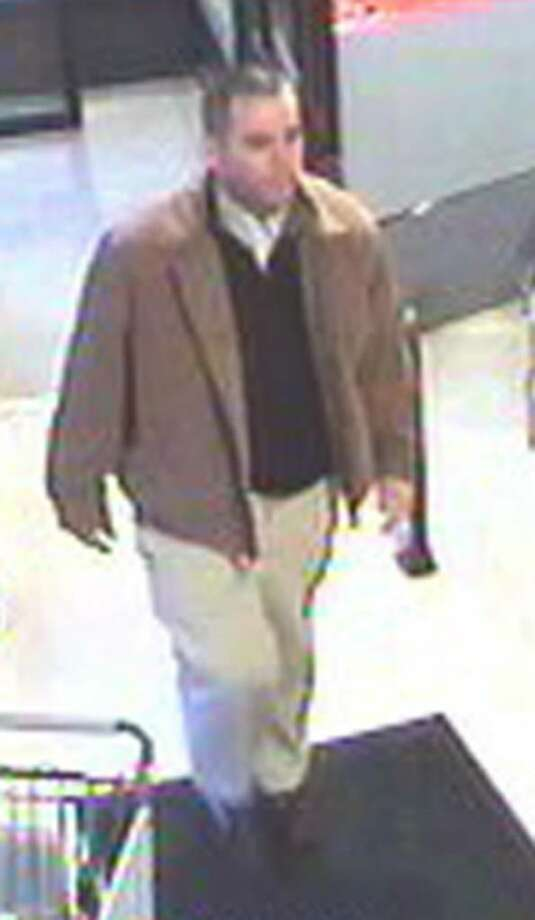 Surveillance camera images of man suspected of spending spree with stolen credit cards. The suspect is described as a white man, about 6 feet tall with a medium build and very short or thinning dark hair. He was dressed in khaki pants and a tan jacket, and wore glasses when he was in one of the stores. He was driving a newer model four-door Jeep Liberty, gold or tan in color, with a retractable roof. Photo: Contributed Photo / Connecticut Post Contributed