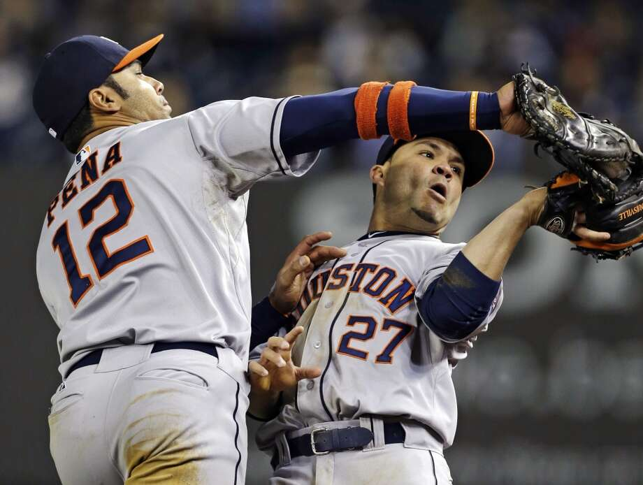 Astros players Jose Altuve and Carlos Pena come close to colliding while trying to catch a ball for an out.