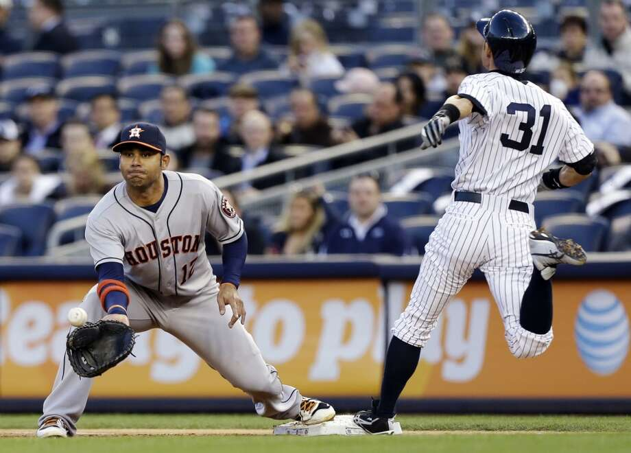 A ball thrown to Astros first baseman Carlos Pena is not in time to tag out Ichiro Suzuki of the Yankees. Photo: Katy Willens, Associated Press