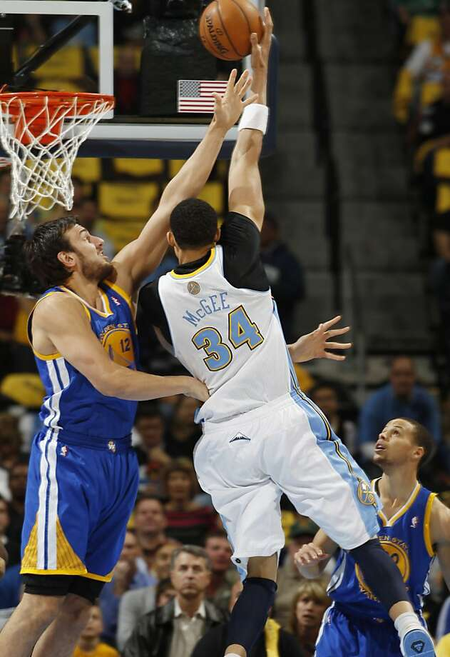 Golden State Warriors center Andrew Bogut, left, of Australia, reaches up to block a shot by Denver Nuggets forward JaVale McGee during the first quarter of Game 5 of their first-round NBA basketball playoff series, Tuesday, April 30, 2013, in Denver. (AP Photo/David Zalubowski) Photo: David Zalubowski, Associated Press
