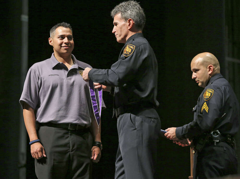 Officer Jonathan Esquivel receives the Purple Heart from Police Chief William McManus. Esquivel was seriously injured in February 2012 when he was hit by a truck at the scene of another accident. Photo: Photos By Tom Reel / San Antonio Express-News