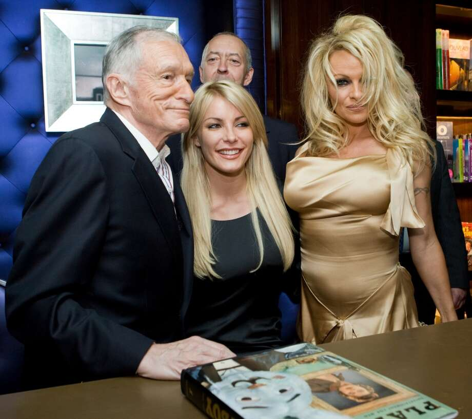Pamela Anderson poses in 2009 with Hugh Hefner and Crystal Harris, center.
