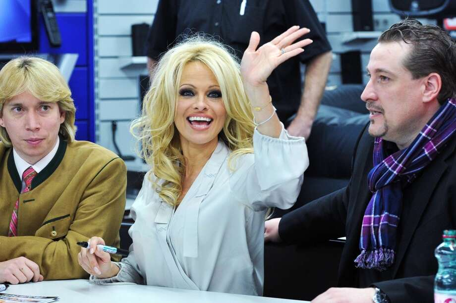 The beginning of the toned-down look? Pamela Anderson signs autographs in Vienna, Austria on March 5, 2012.