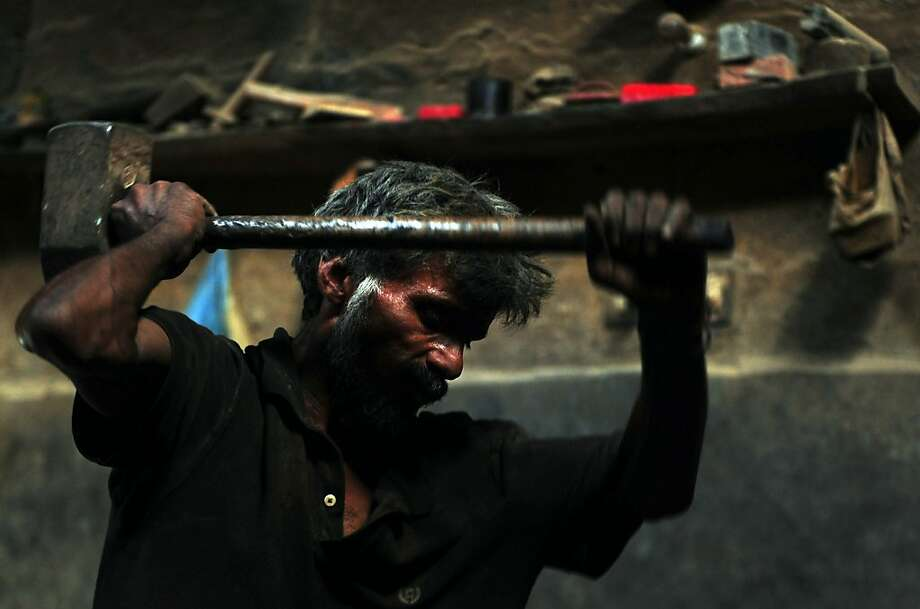 TOPSHOTS A Pakistani labourer uses a hamer as he works at an iron factory in Karachi on April 30, 2013, on the eve of International Labour Day. Pakistan has a workforce of around 56 million people among a population of 179 million, according to Pakistan's official figures compiled by the Federal Bureau of Statistics. AFP PHOTO / ASIF HASSANASIF HASSAN/AFP/Getty Images Photo: Asif Hassan, AFP/Getty Images