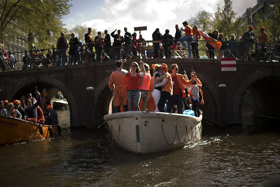 People dance on boats along a canal in Amsterdam as they celebrate the coronation of King Willem-Alexander Tuesday, April 30, 2013. At 46, Willem-Alexander is the youngest monarch in Europe and the first Dutch king in 123 years, since Willem III died in 1890. (AP Photo/Emilio Morenatti) Photo: Emilio Morenatti, Associated Press
