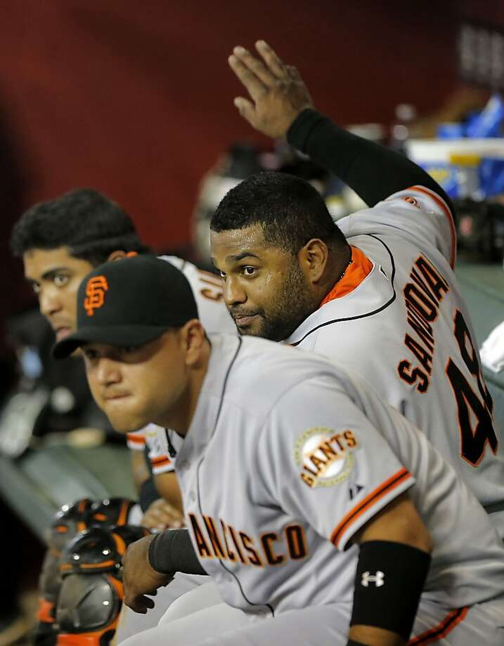 San Francisco Giants players, from left, Hector Sanchez, Pablo Sandoval and Guillermo Quiroz watch the Arizona Diamondbacks hit during the fifth inning of a baseball game, Tuesday, April 30, 2013, in Phoenix. (AP Photo/Matt York) Photo: Matt York, Associated Press