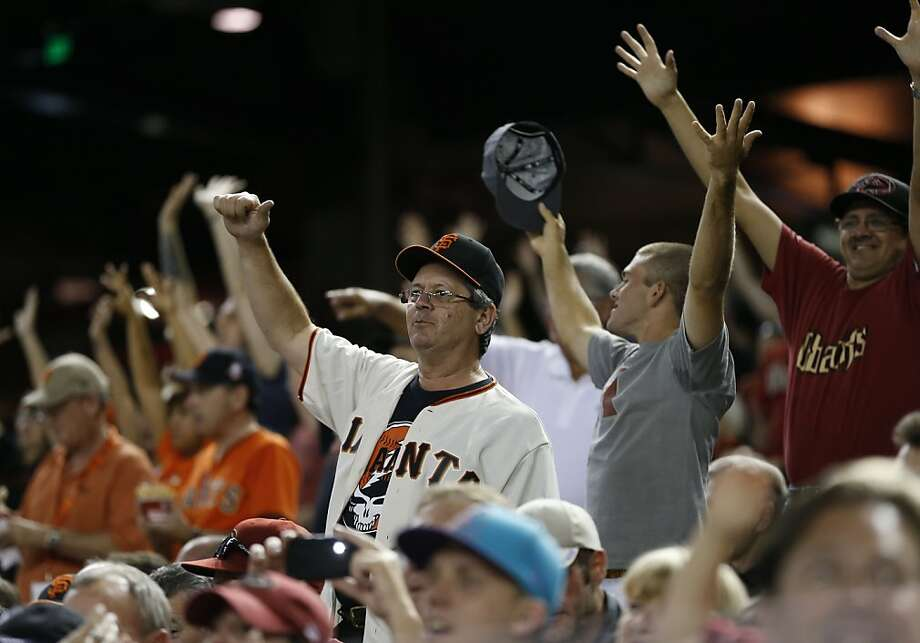 San Francisco Giants and Arizona Diamondbacks fans cheer during the sixth inning of a baseball game, Tuesday, April 30, 2013, in Phoenix. (AP Photo/Matt York) Photo: Matt York, Associated Press