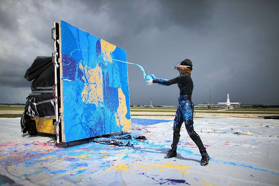 Airbrushed self-portrait: Artist Princess Tarinan von Anhalt throws paint into the exhaust wash of a Flexjet Learjet 40 XR engine (off camera at right) to create a painting marking the 50th anniversary of the Learjet in West Palm Beach, Fla. Photo: Joe Raedle, Getty Images