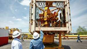 Cameron Wallace (left) and Eric Poller a Subsea Engineer for Helix Well Ops looks at a new oil spill-containment system developed by Houston's Helix Energy Solutions at the Worldwide Oilfield Machine Inc., Wednesday, April 13, 2011, in Houston.