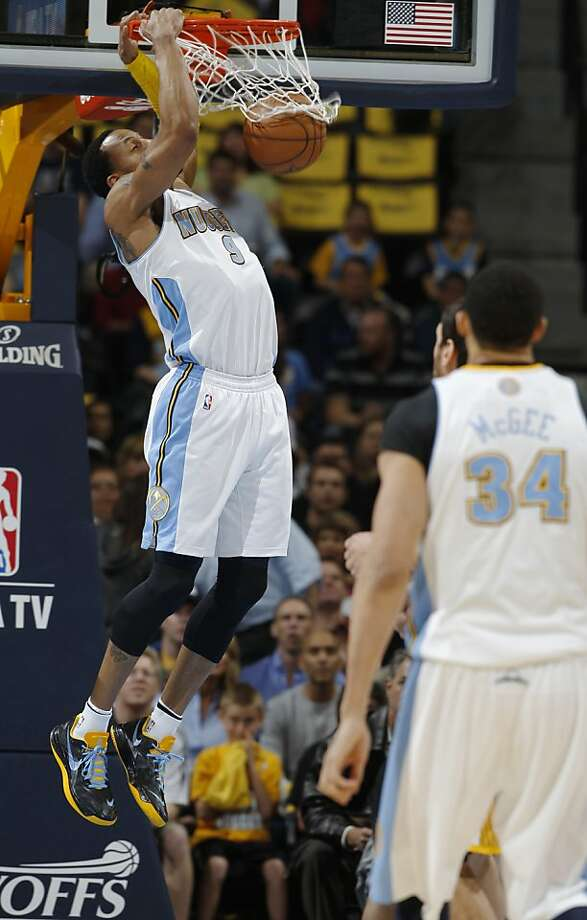 Denver Nuggets guard Andre Iguodala hangs from the rim after dunking against the Golden State Warriors during the first quarter of Game 5 of their first-round NBA basketball playoff series, Tuesday, April 30, 2013, in Denver. (AP Photo/David Zalubowski) Photo: David Zalubowski, Associated Press