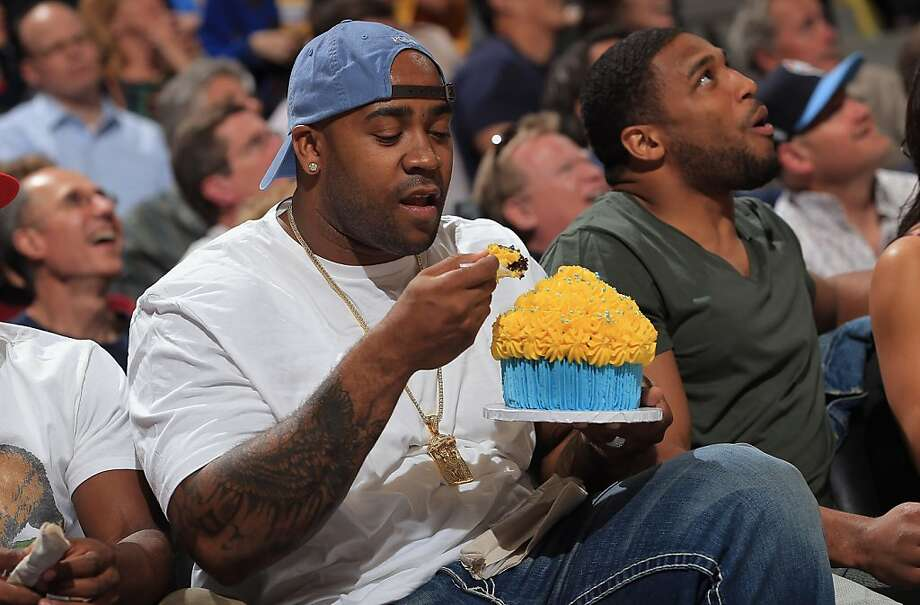 DENVER, CO - APRIL 30:  Defensive tackle Kevin Vickerson of the Denver Broncos is served a large cupcake as he sits courtside with linebacker Wesley Woodyard (R) to see the Golden State Warriors face the Denver Nuggets during Game Five of the Western Conference Quarterfinals of the 2013 NBA Playoffs at the Pepsi Center on April 30, 2013 in Denver, Colorado. The Nuggets defeated the Warriors 107-100. NOTE TO USER: User expressly acknowledges and agrees that, by downloading and or using this photograph, User is consenting to the terms and conditions of the Getty Images License Agreement.  (Photo by Doug Pensinger/Getty Images) Photo: Doug Pensinger, Getty Images