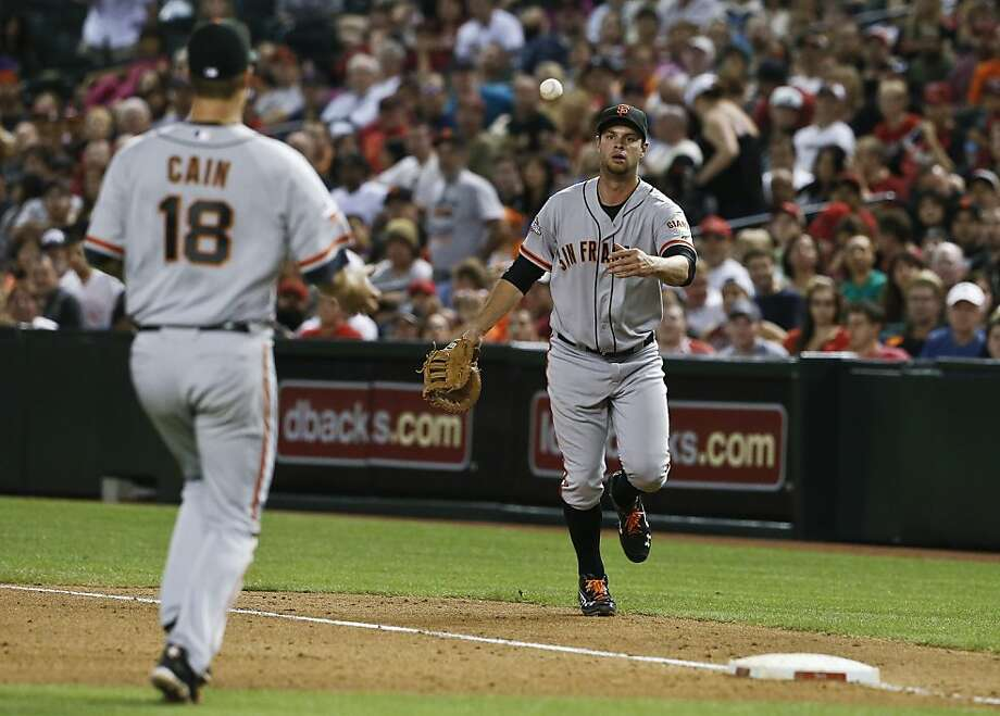 San Francisco Giants' Brandon Belt, right, flips a ball hit by Arizona Diamondbacks' Eric Chavez to pitcher Matt Cain (18) who covers first base for the out during the sixth inning of a baseball game, on Monday, April 29, 2013, in Phoenix.  The Giants defeated the Diamondbacks 6-4. (AP Photo/Ross D. Franklin) Photo: Ross D. Franklin, Associated Press