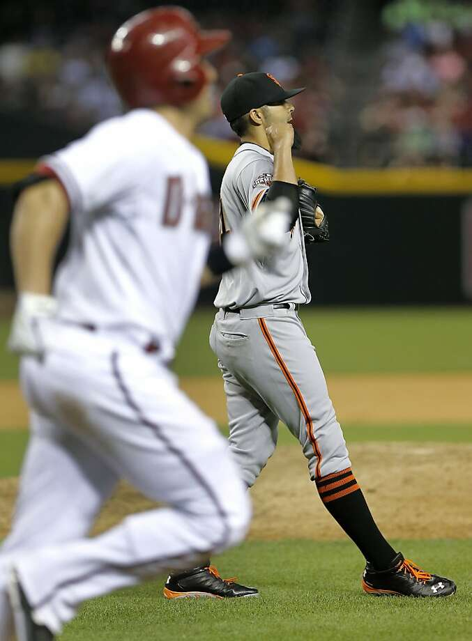 San Francisco pitcher Sergio Romo, right, pumps his fist as Arizona Diamondbacks' Miguel Montero, left, watches his game-ending fly out during the ninth inning of a baseball game, Tuesday, April 30, 2013, in Phoenix. The Giants won 2-1. (AP Photo/Matt York) Photo: Matt York, Associated Press