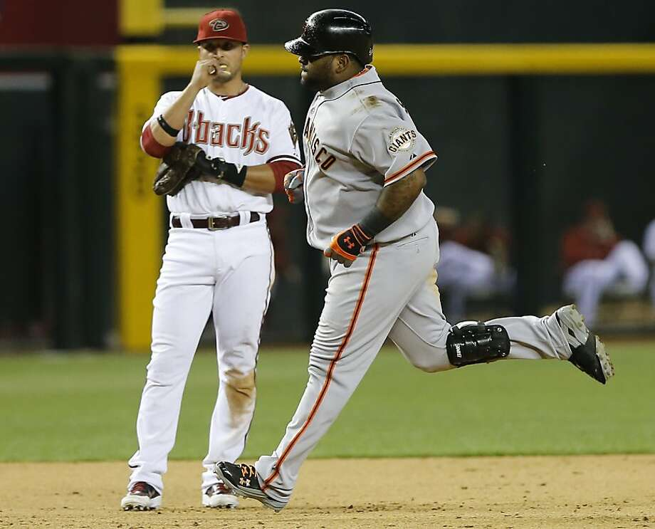 San Francisco Giants' Pablo Sandoval, right, rounds the bases after hitting a two run home run as Arizona Diamondbacks Martin Prado looks on during the ninth inning of a baseball game, Tuesday, April 30, 2013, in Phoenix. (AP Photo/Matt York) Photo: Matt York, Associated Press