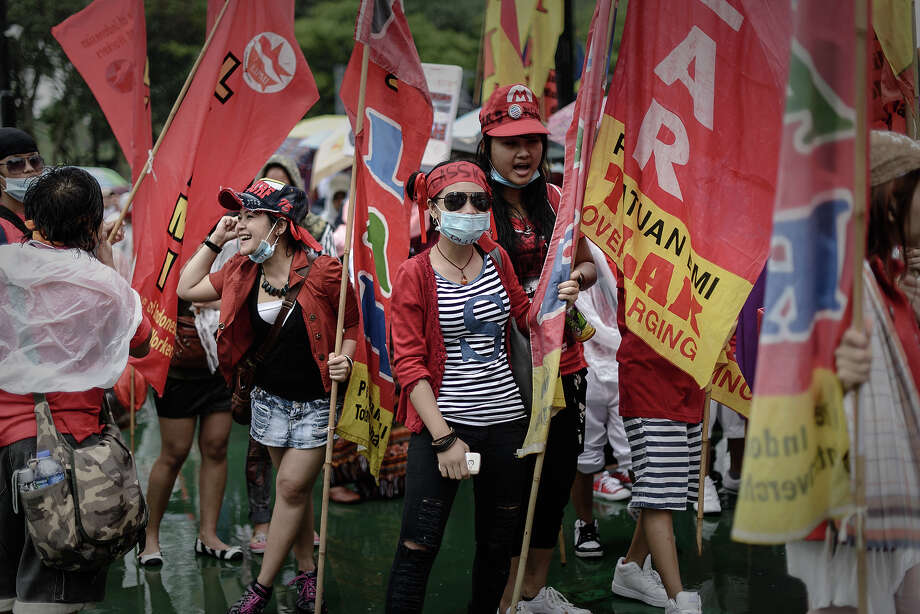 Migrant workers from Indonesia carry flags and banners during a Labour Day rally in Hong Kong on May 1, 2013.  In Hong Kong, one of Asia's beacons of capitalism, trade unions said they were expecting 5,000 people to march in support of striking dock workers. Photo: PHILIPPE LOPEZ, AFP/Getty Images / 2013 AFP
