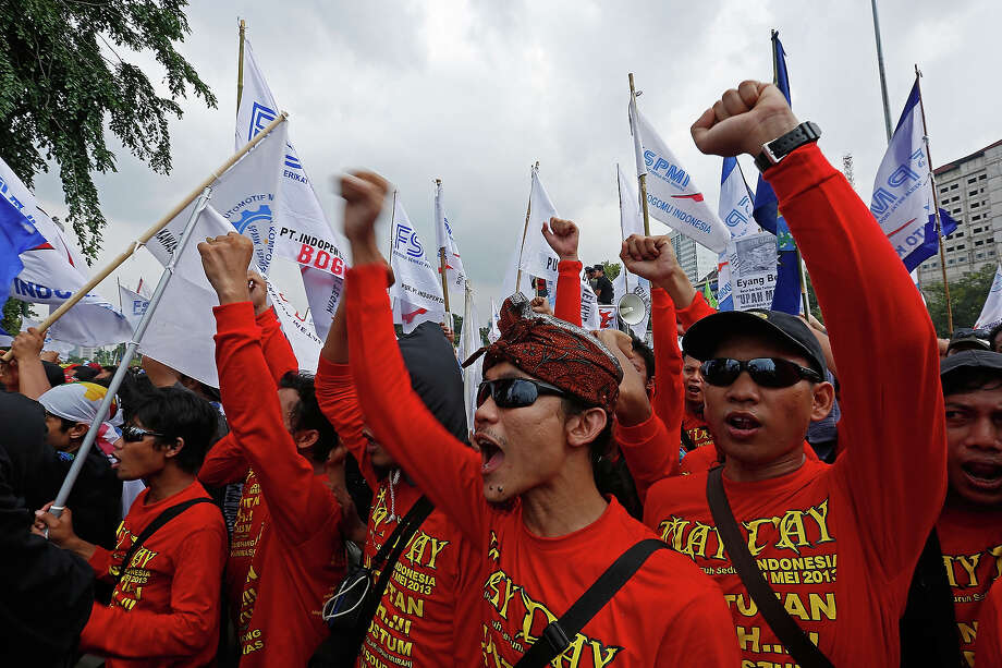 May Day demonstrators shout slogans in front of the Presidential Palace during a labor demonstration on May 1, 2013 in Jakarta, Indonesia.  Tens of thousands of workers and labor activists marched through Jakarta's central business district, demanding the implementation of higher minimum wages and better working conditions. Photo: Ed Wray, Getty Images / 2013 Getty Images