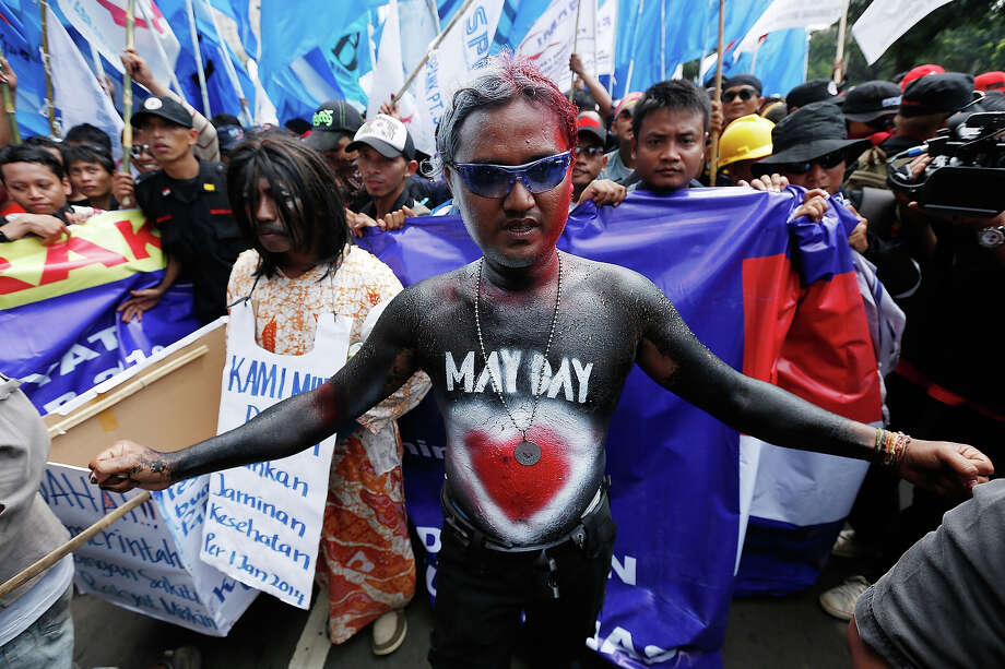 A May Day demonstrator in body paint leads a group of union members and activists in a demonstration in front of the Presidential Palace May 1, 2013 in Jakarta, Indonesia.  Tens of thousands of workers and labor activists marched through Jakarta's central business district, demanding the implementation of higher minimum wages and better working conditions. Photo: Ed Wray, Getty Images / 2013 Getty Images
