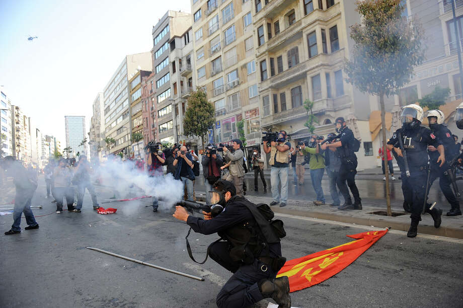 A masked policeman fires teargas during clashes at a May Day demonstration on May 1, 2013 in Istanbul.  Turkish riot police used water cannon and tear gas on Wednesday in a bid to disperse hundreds of protesters who defied a Labour Day ban on demonstrations in a central part of Istanbul. The ban was imposed to avoid trouble during  renovation work taking place at the symbolic Taksim square, a traditional rallying point. Photo: AFP, AFP/Getty Images / 2013 AFP