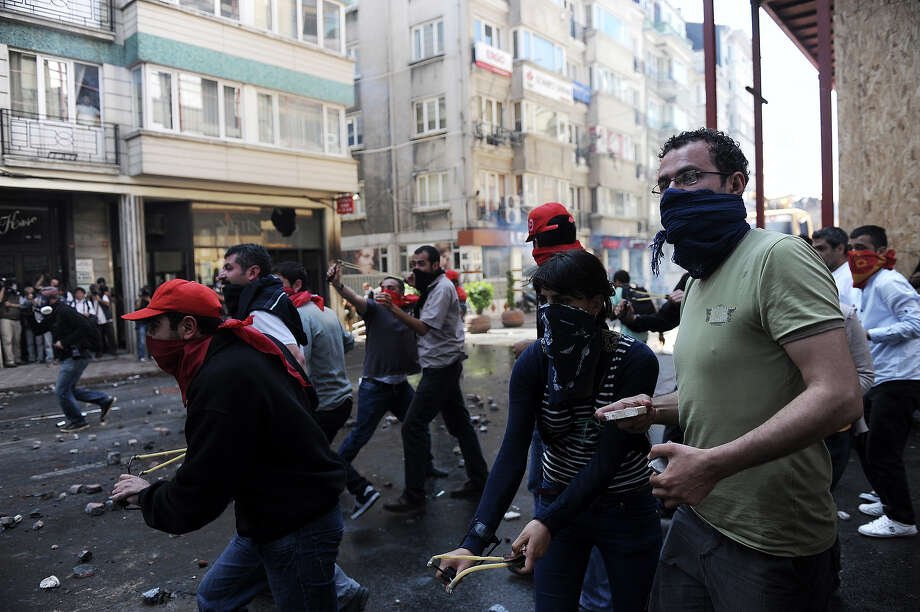 Masked protestors throw objects during clashes at a May Day demonstration on May 1, 2013 in Istanbul.  Turkish riot police used water cannon and tear gas on Wednesday in a bid to disperse hundreds of protesters who defied a Labour Day ban on demonstrations in a central part of Istanbul. The ban was imposed to avoid trouble during  renovation work taking place at the symbolic Taksim square, a traditional rallying point. Photo: AFP, AFP/Getty Images / 2013 AFP