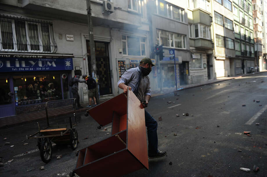 A protestor pulls a table to build a barricade during clashes at a May Day demonstration on May 1, 2013 in Istanbul.  Turkish riot police used water cannon and tear gas on Wednesday in a bid to disperse hundreds of protesters who defied a Labour Day ban on demonstrations in a central part of Istanbul. The ban was imposed to avoid trouble during  renovation work taking place at the symbolic Taksim square, a traditional rallying point. Photo: AFP, AFP/Getty Images / 2013 AFP