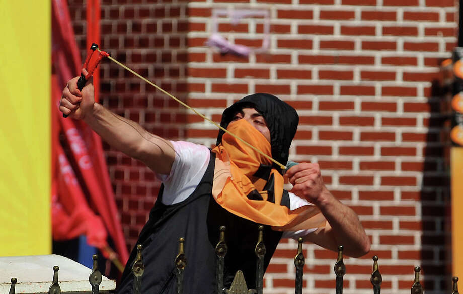 A protestor uses a catapult during clashes at a May Day demonstration on May 1, 2013, in Istanbul.  Several people were injured on Wednesday as Turkish riot police used water canon and tear gas to disperse hundreds of protesters who defied a May Day ban on demonstrations in a central part of Istanbul. Photo: AFP, AFP/Getty Images / 2013 AFP