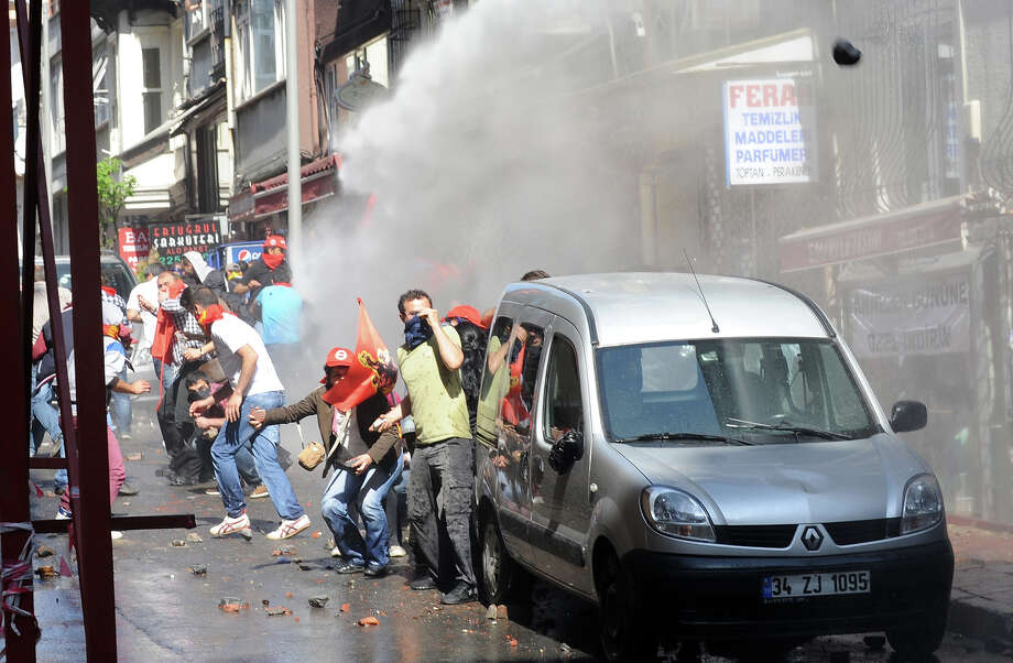 Protestors throw stones during clashes with police at a May Day demonstration on May 1, 2013, in Istanbul.  Several people were injured on Wednesday as Turkish riot police used water canon and tear gas to disperse hundreds of protesters who defied a May Day ban on demonstrations in a central part of Istanbul. Photo: AFP, AFP/Getty Images / 2013 AFP