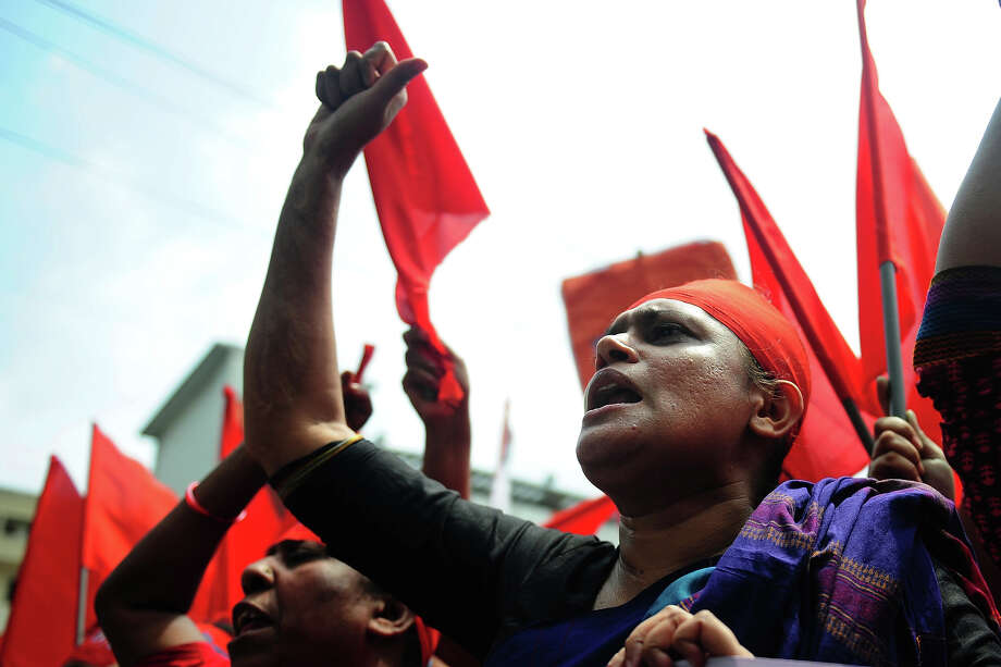 Bangladeshi activists shout slogans and wave flags during a procession to mark May Day or International Workers Day in Dhaka on May 1, 2013. Tens of thousands of Bangladeshis joined May Day protests Wednesday to demand the execution of textile bosses over the collapse of a factory complex, as rescuers warned the final toll could be more than 500. Photo: MUNIR UZ ZAMAN, AFP/Getty Images / 2013 AFP